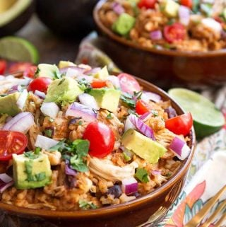 Instant Pot Chicken Taco Bowls are an easy dump and start meal with lots of delicious taco flavor. It doesn't get much simpler than this! These pressure cooker chicken taco bowls are also a delicious meal prep recipe. simplyhappyfoodie.com #instantpotchickentacobowls #pressurecookertacobowls #instantpotburritobowls