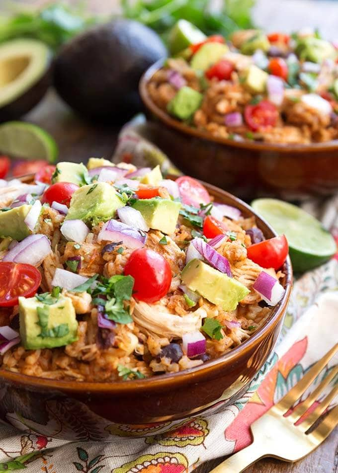 Two Chicken Taco Bowls in brown bowls topped with diced red onion, avocado, and cherry tomatoes