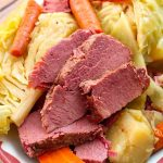 Corned Beef and Cabbage on a white plate with red boarder