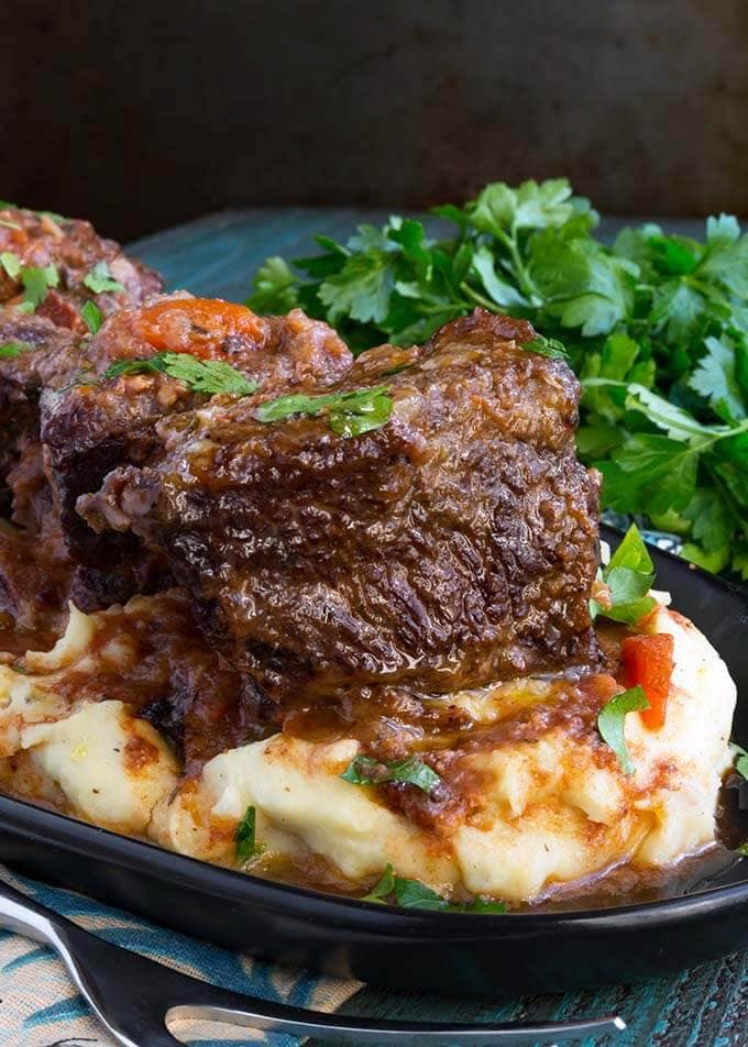 Short Ribs over mashed potatoes on a black plate next to a bunch of fresh parsley