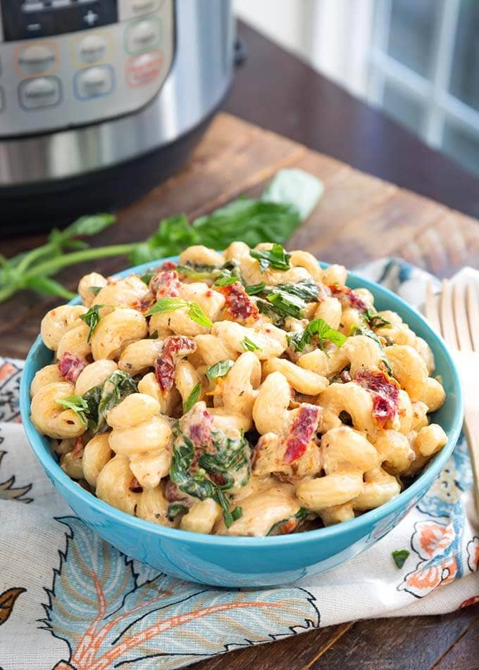 Tuscan Chicken Pasta in a blue bowl in front of a pressure cooker