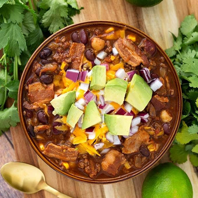 Slow Cooker Beefy Bacon Chili is a very hearty, meaty chili with a little kick of spice, and a lot of flavor! My taste testers all agreed that this is one of their favorite chili recipes! A perfect crock pot chili recipe! simplyhappyfoodie.com #slowcookerchili #crockpotchili #bestslowcookerchili