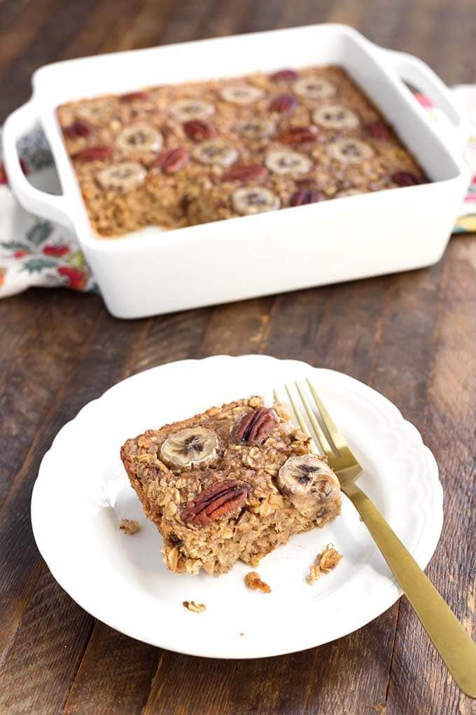 Slice of Banana Bread Baked Oatmeal on white plate with fork in front of white baking dish