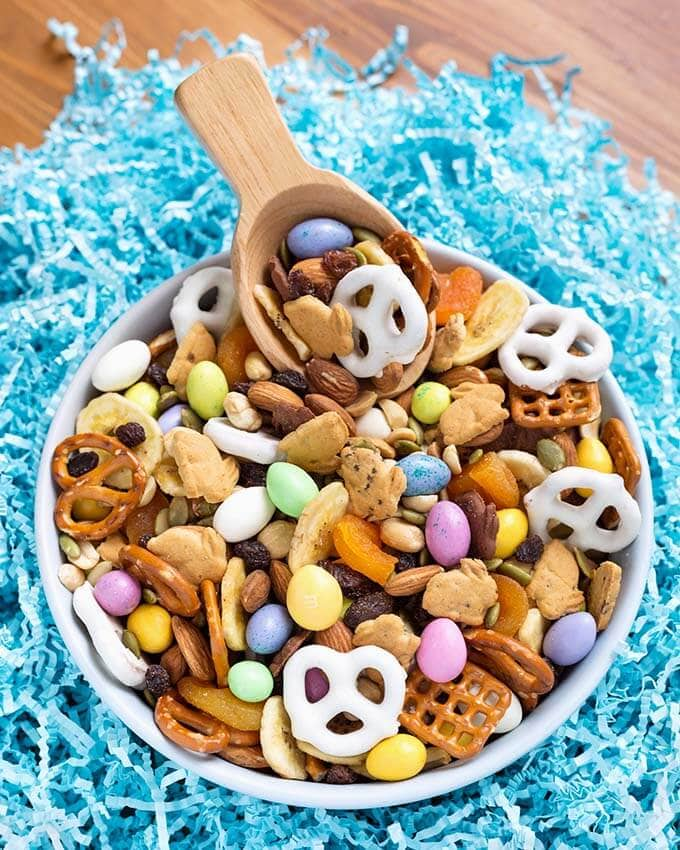 Bunny Bait Easter Trail Mix in a white bowl with wooden serving spoon on top of shredded light blue confetti paper
