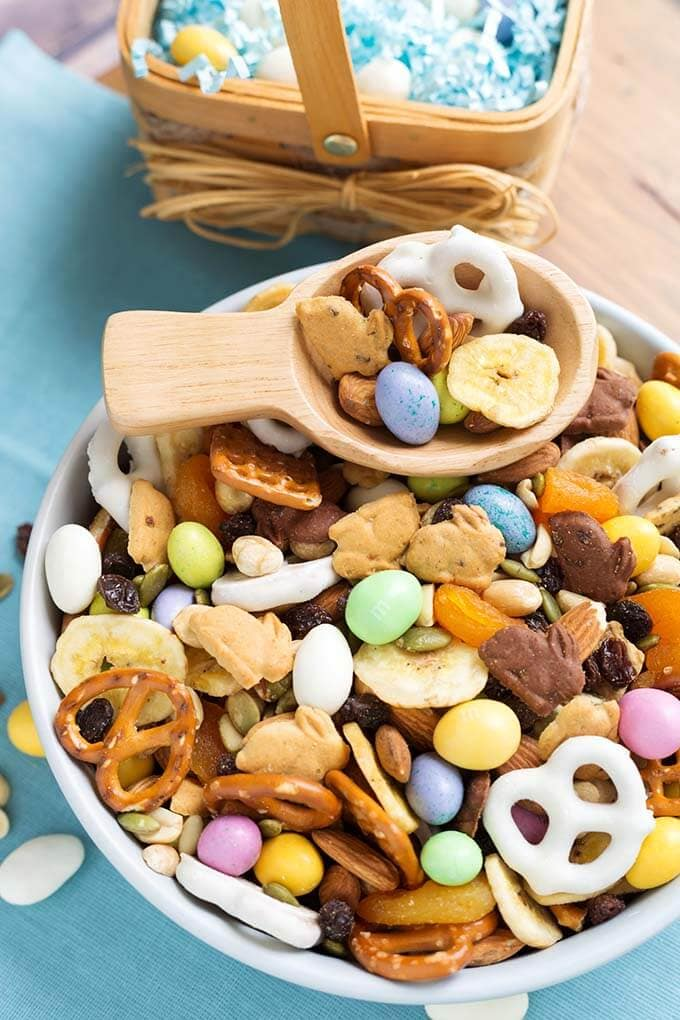 Bunny Bait Easter Trail Mix in a white bowl with wooden serving spoon in front of small basket