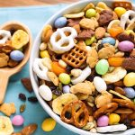 Bunny Bait Easter Trail Mix in a white bowl next to a wooden serving spoon all on a blue napkin
