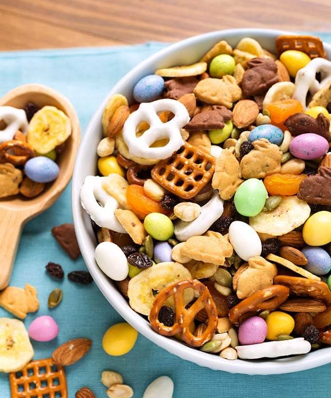 Bunny Bait Easter Trail Mix in a white bowl next to a wooden spoon on a blue napkin