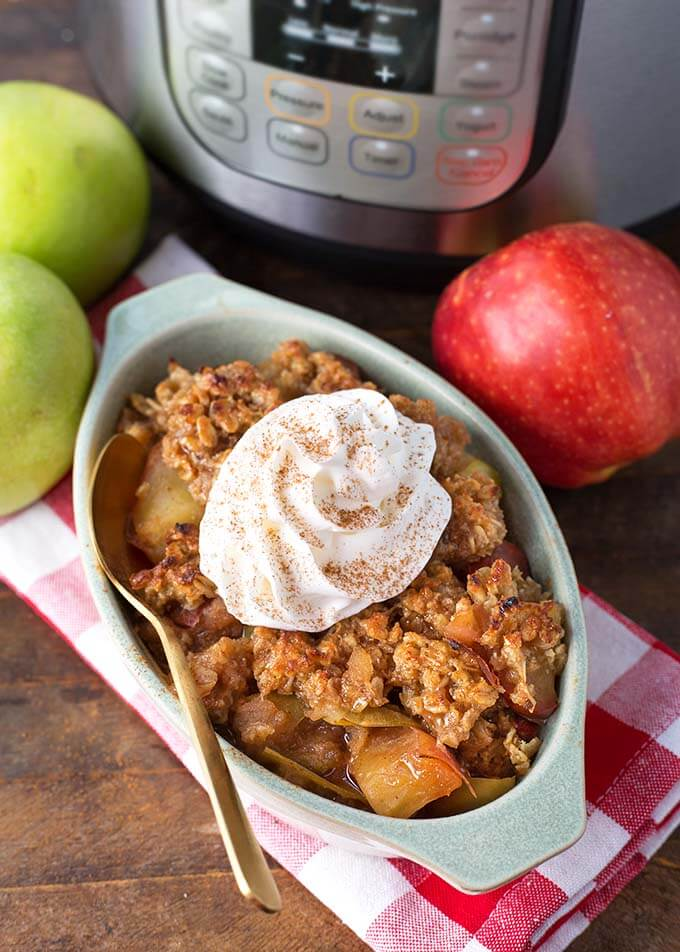 Apple Crisp in oblong gray baking dish topped with whipped cream in front of apples and pressure cooker