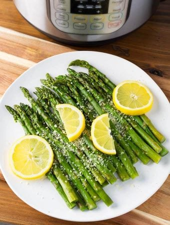Asparagus on a white plate with lemon slices