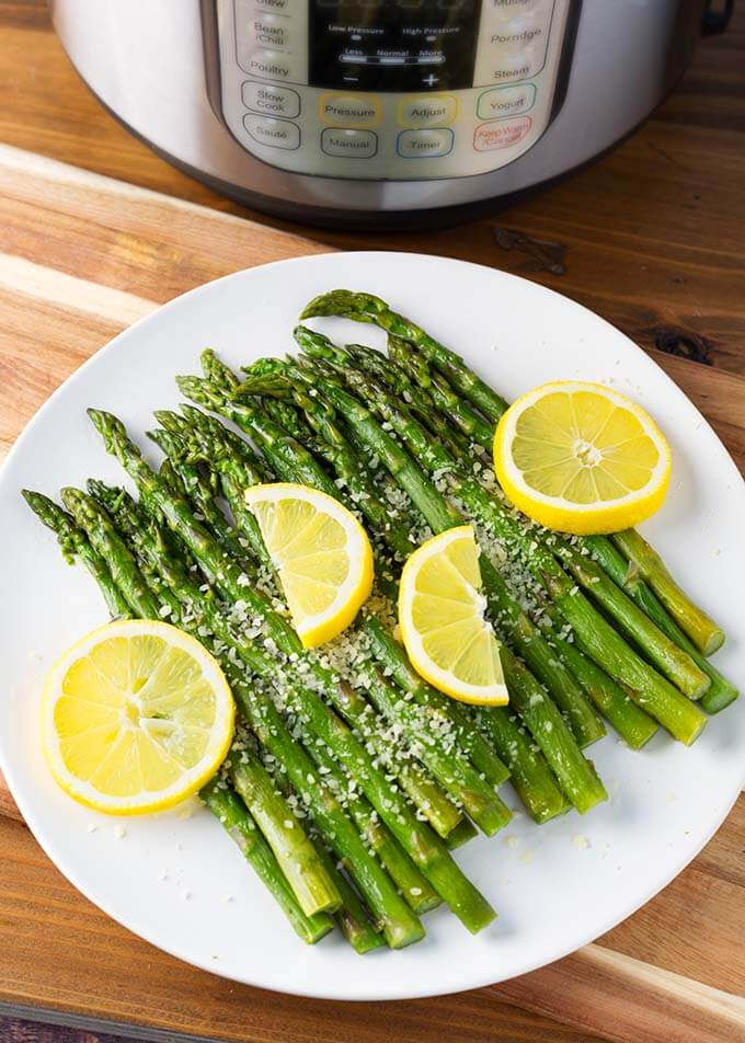 Asparagus on a white plate with lemons in front of pressure cooker