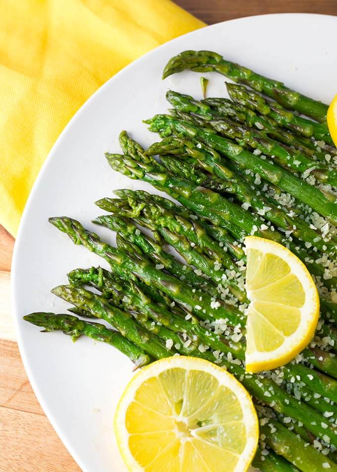 Close up of Asparagus on white plate with lemon