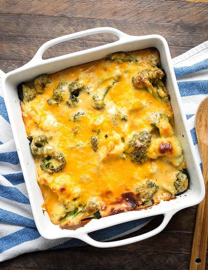 Broccoli Cauliflower Cheese Bake in a white square baking dish on a white and blue stripped napkin