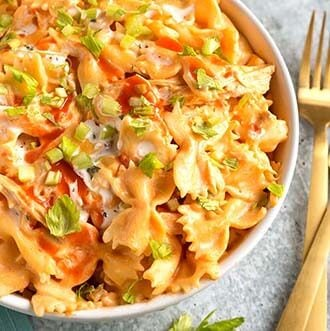 instant pot buffalo chicken pasta in a white bowl next to golden forks