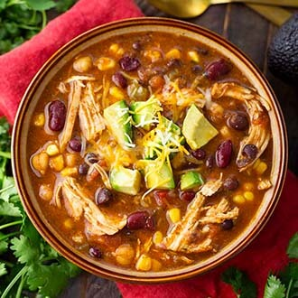 Instant Pot Chicken Taco Soup in a brown bowl on top of a red napkin