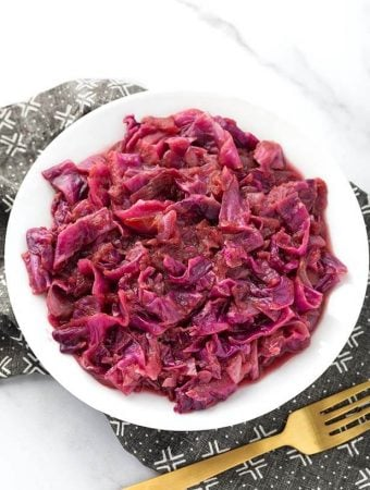 German Red Cabbage on a white plate next to golden fork on top of a black patterned napkin