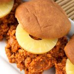 Hawaiian BBQ Sloppy Joes with slice of pineapple on a hamburger bun