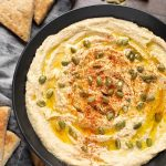 Hummus in black bowl next to cut pieces of flatbread