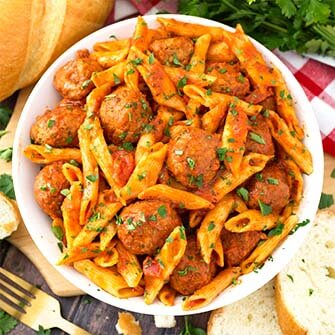 meatball pasta dinner on a white plate next to sliced french bread