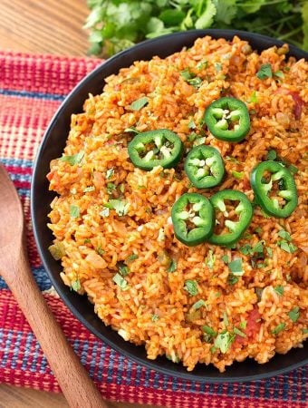 Mexican Rice on a black plate on top of a red and blue stripped mat