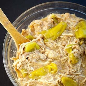 instant pot mississippi chicken in glass bowl with wooden mixing spoon