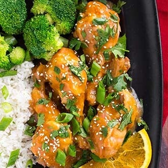 instant pot orange chicken legs with rice and broccoli on black plate