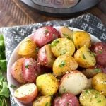 Potatoes with Herb Butter in a white bowl in front of a pressure cooker