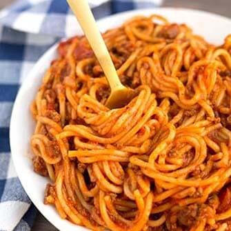 spaghetti on a white plate with gold fork