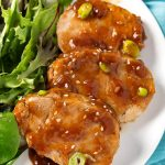 Sliced Teriyaki Pork Tenderloin with leafy green vegetables on white plate