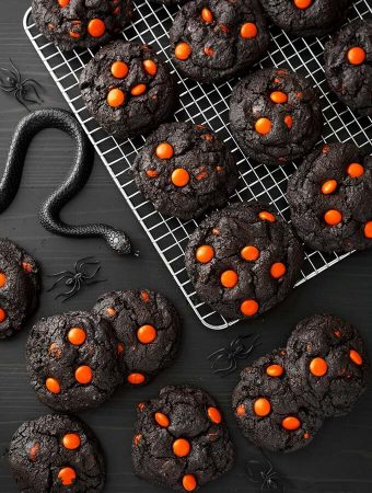 Dark Chocolate Halloween Cookies on cooling rack next to black plastic spiders and snakes