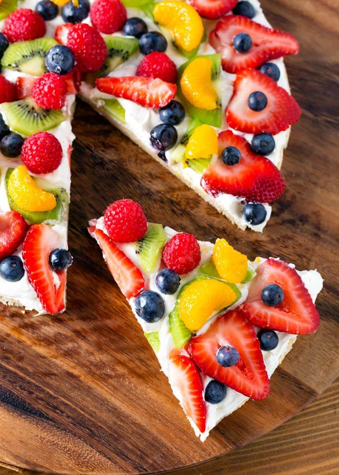 Slice of Fresh Fruit Pizza being removed from the whole