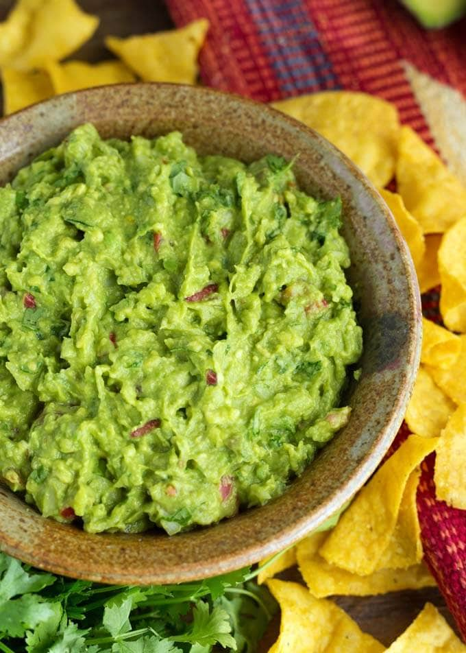 Fresh Homemade Guacamole in a brown bowl next to corn tortilla chips