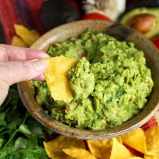 Hand dipping corn tortilla chip into Fresh Homemade Guacamole