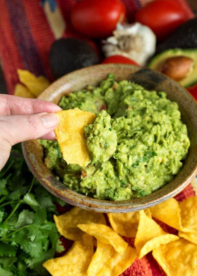 Hand dipping corn tortilla chip into brown bowl of Fresh Homemade Guacamole
