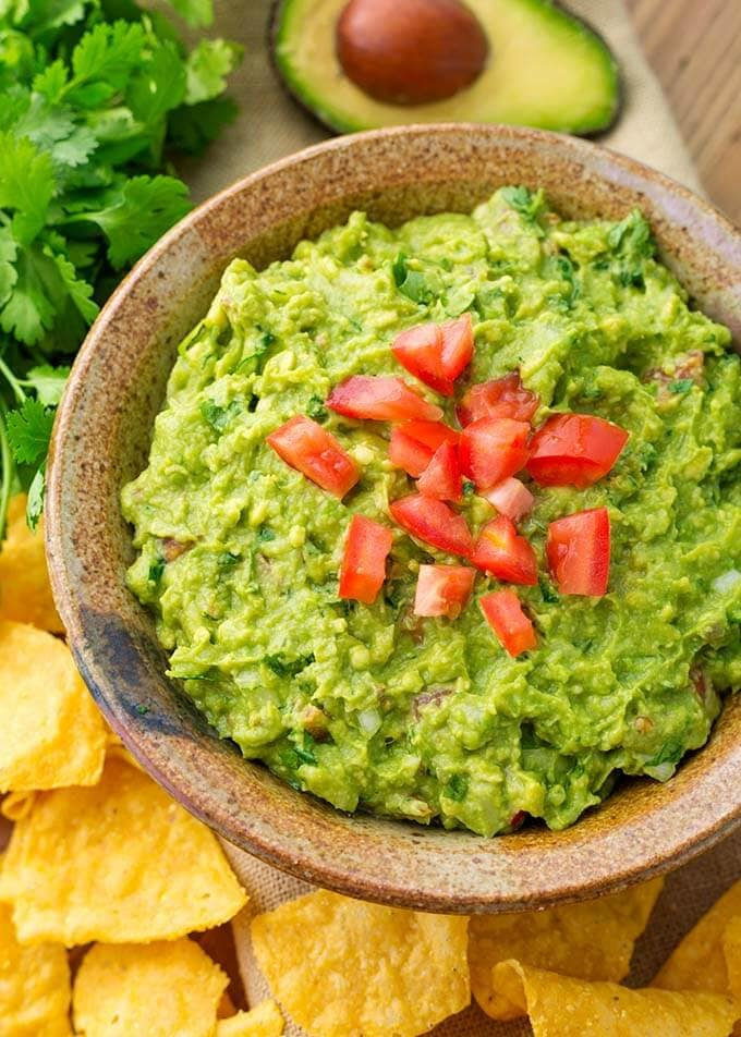 Fresh Homemade Guacamole in brown bowl topped with diced tomatoes next to corn tortilla chips