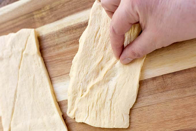 hand pinching the seam of croissant dough together