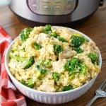 Chicken Broccoli Rice Casserole in a white bowl in front of a pressure cooker