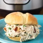 Crack Chicken on hamburger bun on blue plate in front of pressure cooker