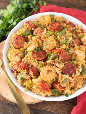 Jambalaya in a white bowl on a wooden board