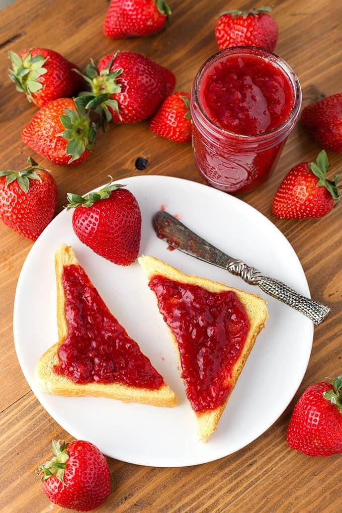Strawberry Jam spread on cut toast on white plate with strawberries and silver knife in front of jar