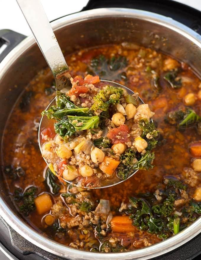 Closeup of ladle full of Tuscan Sausage Kale Soup over pressure cooker