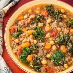 Tuscan Sausage Kale Soup in brown bowl on wooden board