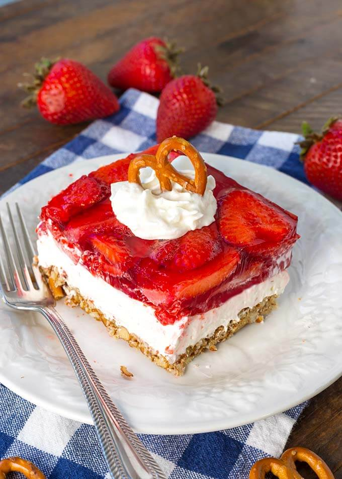 Slice of Strawberry Pretzel Jello Salad on white plate with silver fork on blue gingham napkin