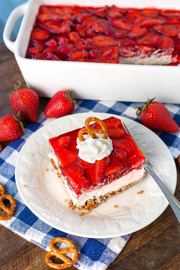 Slice of Strawberry Pretzel Jello Salad on white plate in front of white baking dish