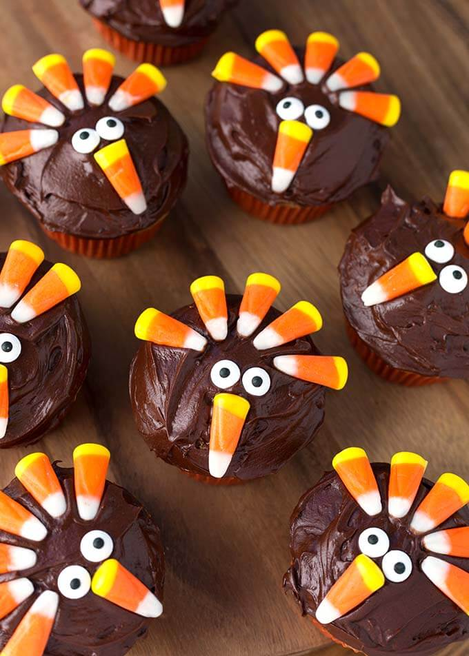 Several Candy Corn Turkey Thanksgiving Cupcakes on a wooden board