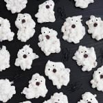 White Chocolate Halloween Ghosts and black plastic spiders on dark wood background
