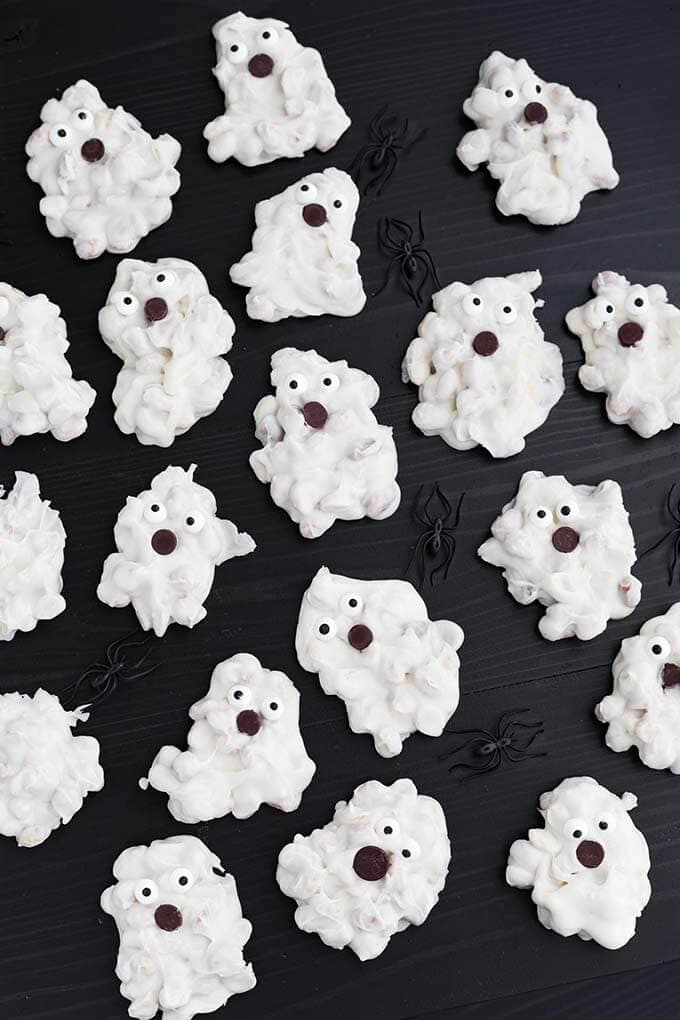 Several White Chocolate Halloween Ghosts and black plastic spiders on dark wood background