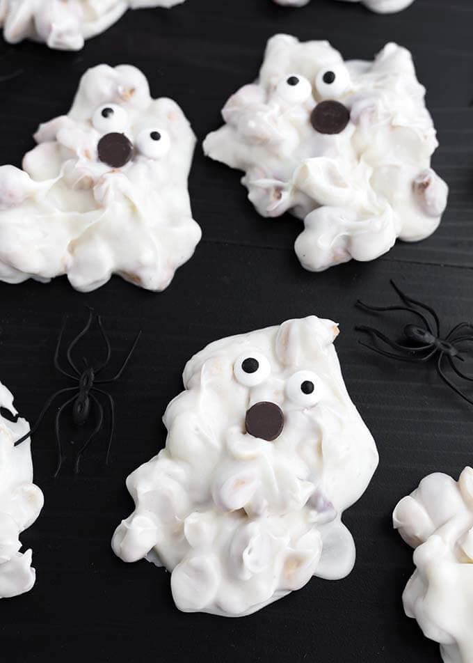 Closeup of White Chocolate Halloween Ghosts on a dark wood background with black plastic spiders