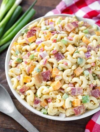 Classic Macaroni Salad in white bowl next to red gingham napkin and silver spoon
