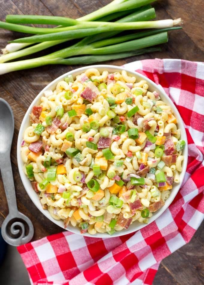 Top view of Classic Macaroni Salad in white bowl next to red gingham napkin and silver spoon