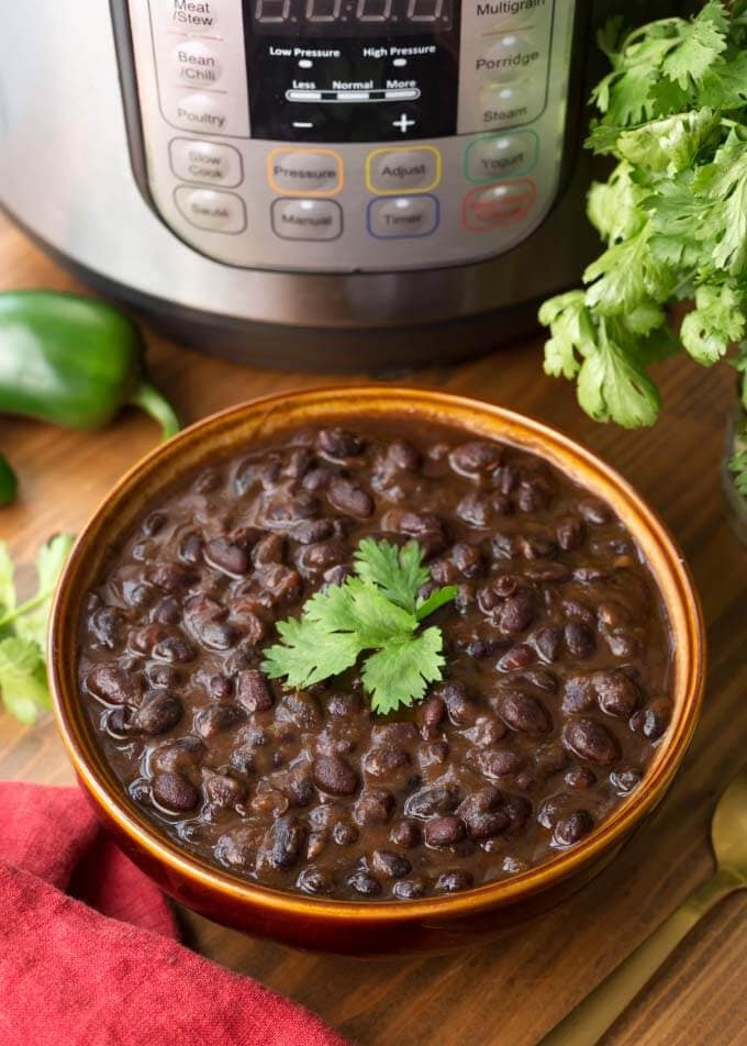 Cuban Black Beans in a brown bowl in front of pressure cooker